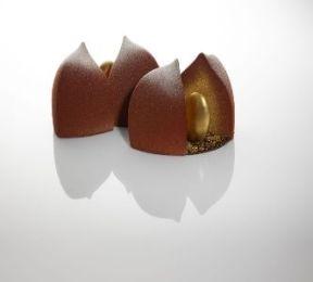 Fauchon - Noël enchanté. Cette bûche est composée d'une mousse de chocolat noir et garnie d'une pâte de kumquats. Ce dessert renferme à sa base un biscuit aux brisures de marrons glaçés et de farine de châtaignes torréfiées dans un habit de velours de chocolat noir et s'accompagne d'une amande d'or qui renferme une purée de Kumquat. 60€/6-8pers