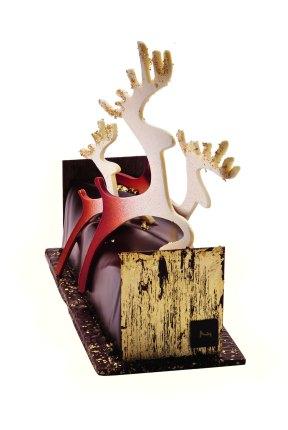La Maison du Chocolat. Délicieuse envolée. Bûche composée d'un fin biscuit sacher aux amandes, sabayon et fine gelée au champagne Blanc de Noir, dés de poire Williams rouge des Alpes poêlés et flambés à l'alcool de poire, mousse au chocolat pure Origine Madagascar, cuvés exclusive. Socle de plaque croquante de chocolat. Embouts en chocolat recouverts de feuille d'or. Décor de rennes en chocolat ivoire, pulvérisés de chocolat noir. 120€/6-8pers