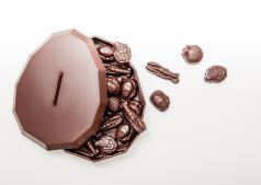 Manufacture de chocolat d'Alain Ducasse : La Manufacture a imaginé cette année une création surprenante : un œuf qui se présente à plat, sous la forme d'une boite dont les formes biseautées évoquent la géométrie de notre tablette signature. Ouvrez... et dégustez les fritures qu'il abrite généreusement en son cœur. Son coffret sur-mesure lui permet de voyager facilement. Une création originale de Pierre Tachon. En chocolat noir uniquement - garni de fritures en praliné enrobé de chocolat noir - 65 € l'œuf